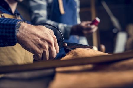 Closeup of craftsman cutting leather handicraft