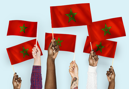 Hands waving the flags of Morrocco