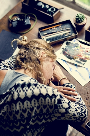 Rear view of artist woman taking a nap on work table