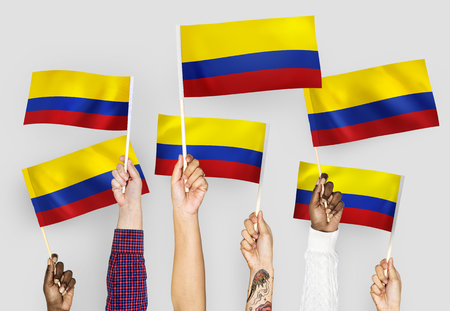 Hands waving the flags of Columbia