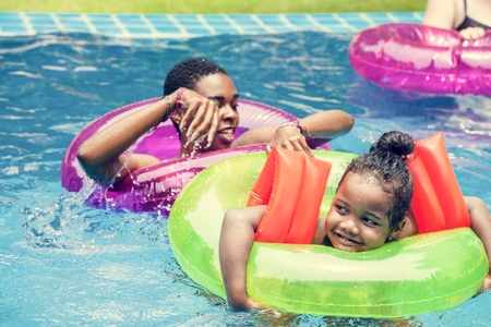 Closeup of black mother and daughter enjoying the pool with inflatable tubes Banco de Imagens