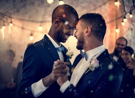 Homosexuelles Paar, das am Hochzeitstag tanzt