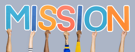 Diverse hands holding the word mission Stock Photo