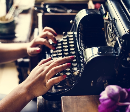 Woman typing vintage typewriter on wooden table Imagens