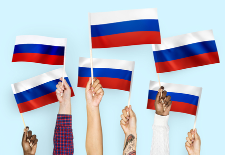 Mani che sventolano le bandiere della Russia Archivio Fotografico