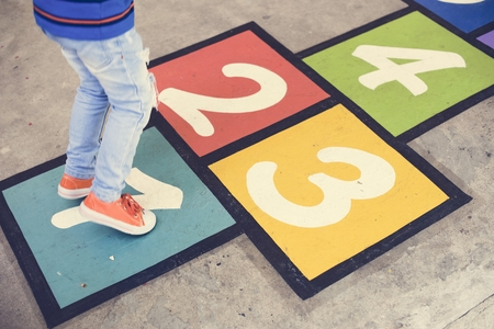 Kid playing hopscotch at school Stockfoto