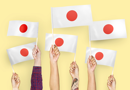Hands waving the flags of Japan