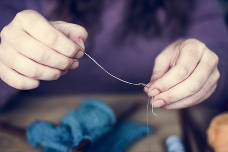 Closeup of hands with thread and needle sewing tools Stok Fotoğraf - 104736296