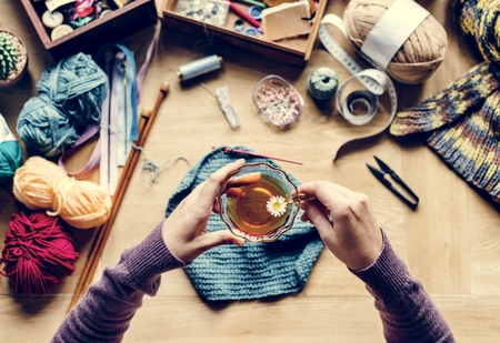 Aerial view of hands holding tea cup with knitting on wooden table