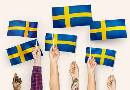 Hands raising Sweden national flags Stock Photo