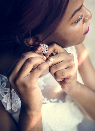 Black bride putting on earrings on her wedding day