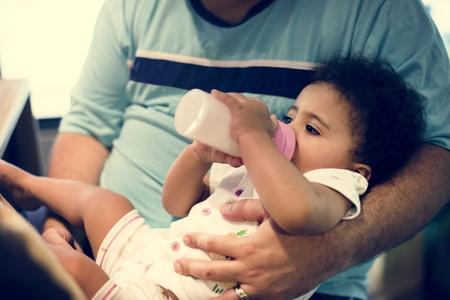 Little girl feeding from formula bottle