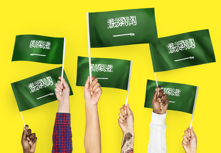 Hands waving the flags of Saudi Arabia Banque d'images