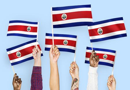 Hands waving the flags of Costa Rica Stok Fotoğraf