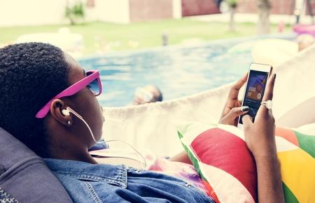 Closeup of black woman using mobile phone listening music Banco de Imagens