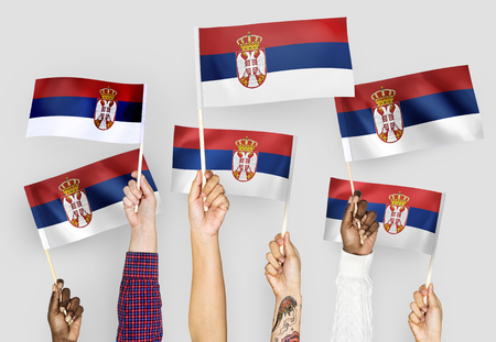 Hands waving the flags of Serbia Stock Photo - 104736711