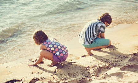 Little children playing sand by the seashore Stock Photo