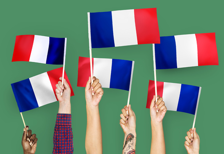 Hands waving the flags of France