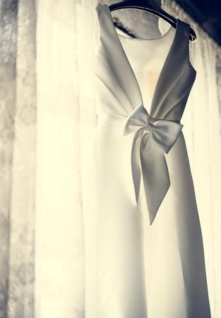 White Wedding Dress Hanging by the Window Фото со стока