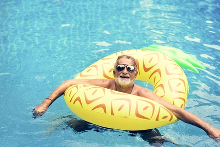 Senior caucasian man floating in the pool with inflatable tube