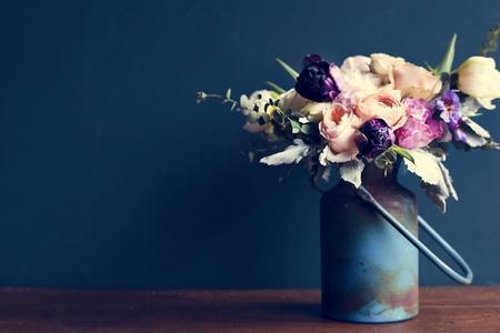 Various fresh flowers arrangement in metalic vase on wooden table Archivio Fotografico - 104737225