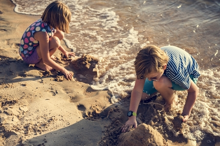 Closeup of caucasian kids playing with the sand together at the beach