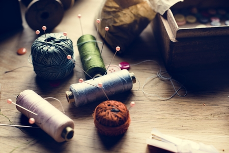 Sewing spools tools on a wooden table Stock Photo