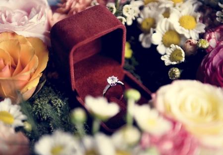 Nahaufnahme des Eherings in der roten Box mit Blumen-Arrangement-Dekoration Standard-Bild