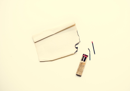 Aerial view of matched with box and burnt paper on white background