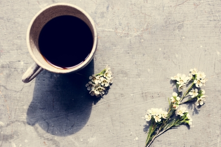 Aerial view of coffee cup with waxflowers