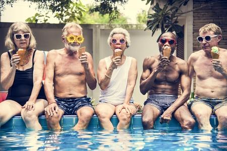 Groep diverse oudere volwassenen die samen roomijs eten Stockfoto
