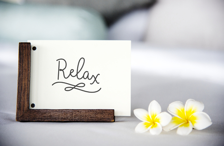 Card on a bed with plumeria flowers mockup