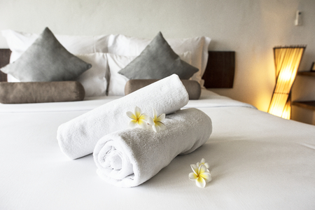 Rolled up clean towels on a bed Stock Photo