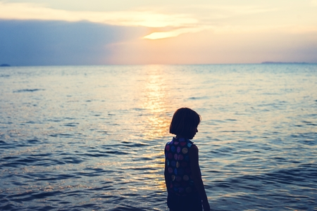 Silhouette rear view of young caucasian girl at the beach alone