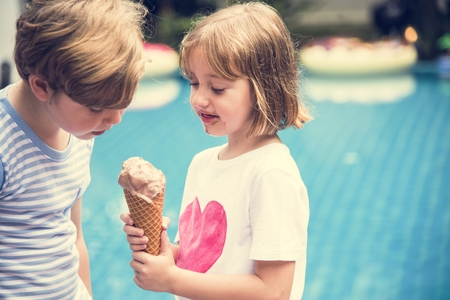 Closeup of young caucasian sibling sharing ice cream together