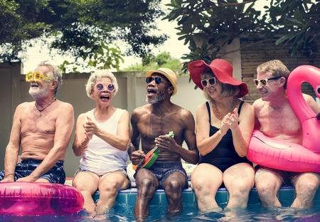 Group of diverse senior adults sitting by the pool enjoying summer together Reklamní fotografie
