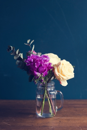Fresh flowers arrangement in a vase on wooden table