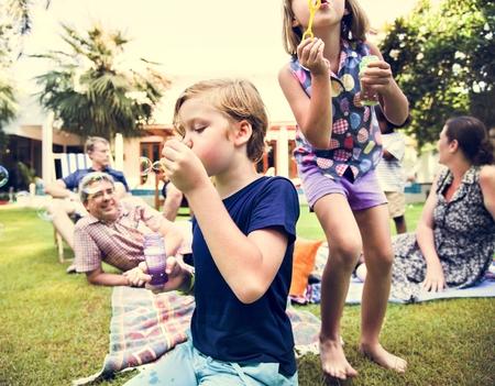 Kids enjoying blowing bubble outdoors