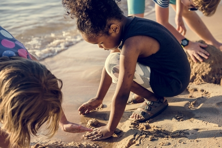 Closeup of diverse kids playing with the sand together at the beach