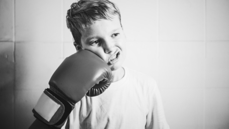 Little boy being playful with a boxing glove Stock fotó