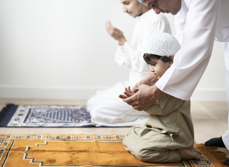 Muslim boy learning how to make Dua to Allah Stockfoto