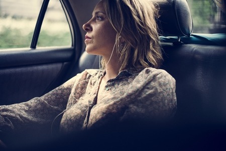 Blond woman sitting in a taxi Stock Photo