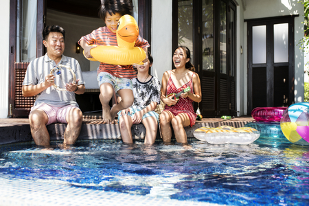 Family playing in a pool Stock Photo - 105391158