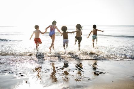 Kids running at the beach Stock Photo