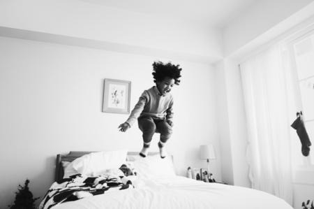 African kid having a fun time jumping on the bed Reklamní fotografie