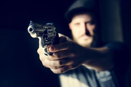 Homme tenant une arme à feu avec fond noir Banque d'images