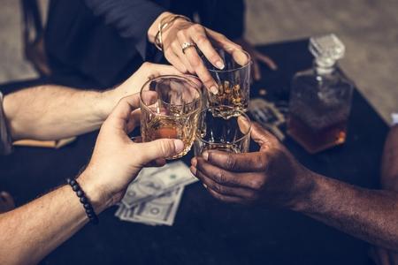 Diverse mani tintinnano bicchieri di alcol