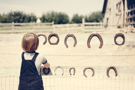 Little girl playing with horseshoe