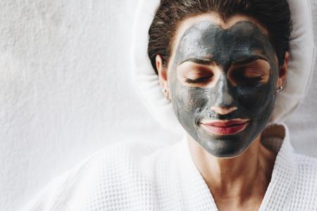 Frau, die mit einer Holzkohle-Gesichtsmaske entspannt