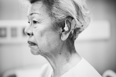 An elderly woman with hearing aids